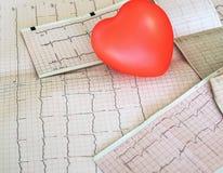 Cardiogram met klein rood hart op de lijstachtergrond stock foto's