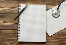 Cardiogram, notitieboekje, pen, stethoscoop op houten lijst royalty-vrije stock afbeelding