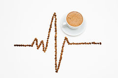 Cardiogram shape made from coffee beans with a cup of coffee on Stock Photos