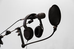Cardioid condenser microphone, headphones and pop filter on a gray background. Home recording Studio Stock Images