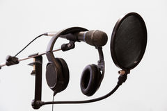 Cardioid condenser microphone, headphones and pop filter on a gray background. Home recording Studio Stock Image