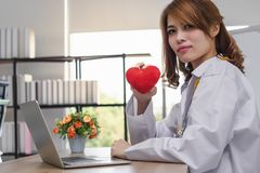 Cardiologist Asian female doctor with red heart in hands. Healthy care and medical concept. Cardiologist Asian female doctor with red heart in hands. Healthy royalty free stock photography