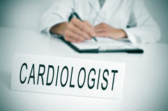 Cardiologist. A doctor sitting in the desk of his consulting room writing in a clipboard and a nameplate with the word cardiologist written in it Royalty Free Stock Photography