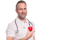Cardiologist holding a red apple to his heart Stock Photography