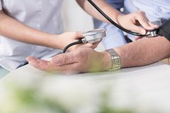 Cardiologist measuring blood pressure Royalty Free Stock Photos