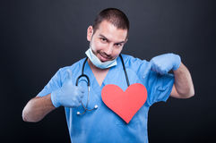 Cardiologist pointing his red heart shape showing like Royalty Free Stock Photos