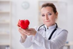 The cardiologist with red heart in medical concept. Cardiologist with red heart in medical concept royalty free stock photos