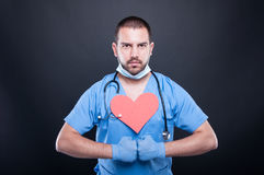 Cardiologist with red heart shape posing strong Stock Image