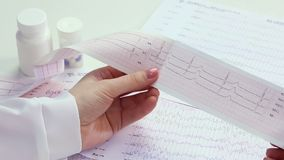 Cardiologist studying patient's heart activity, examining electrocardiogram, EKG stock footage