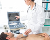 Cardiologist using sonogram on male patient Stock Images