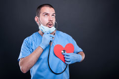 Cardiologist using stethoscope on red shape heart Stock Images