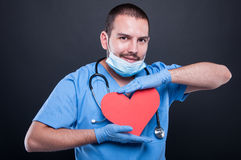 Cardiologist wearing scrubs holding red heart shape Stock Image