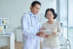 Cardiologista asiático Analyzing Electrocardiogram fotografia de stock