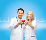 Cardiologistas de sorriso dos doutores com coração Imagens de Stock