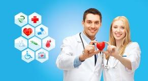 Cardiologistas de sorriso dos doutores com coração vermelho pequeno Fotos de Stock Royalty Free