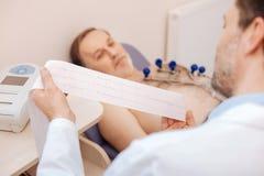 Cardiologo formato eccellente che studia con attenzione il cardiogramma dei pazienti Fotografie Stock Libere da Diritti