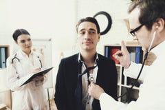 Cardiologue qualifié écoutant le battement de coeur patient du ` s avec le stéthoscope dans le bureau médical photos stock