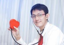 Cardiologue vérifiant le coeur rouge avec le stéthoscope escroquerie de cardiologie Photographie stock