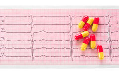 Cardiology. Macro of ECG graph and cardio pills Royalty Free Stock Photography