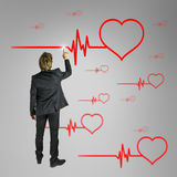 Cardiology concept. Male cardiologist choosing heart shape beating cardiogram on virtual screen stock photography