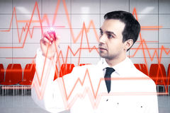 Cardiology concept. Young male doctor drawing abstract heartbeat line on interior background. Cardiology concept Royalty Free Stock Image