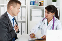 Cardiology and heart health concept. Concerned beautiful female medicine doctor listening carefully patient complaints. Medical care or insurance concept Stock Image