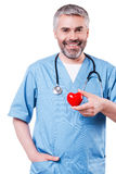Cardiology surgeon. Confident mature cardiology surgeon holding heart shape toy and smiling while standing isolated on white Royalty Free Stock Photos
