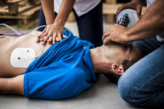 Cardiopulmonary resuscitation. Rescuer making cardiopulmonary resuscitation and defibrillation after heart attack royalty free stock photo