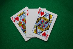 Cards ace king queen of hearts on green felt royalty free stock images