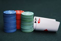Cards aces and chips on green casino game table. Cards aces and stack of chips red, green and blue color on green casino game table royalty free stock photo