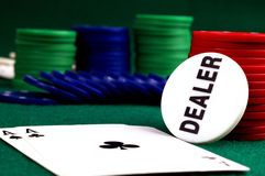 Cards astack of Poker chipsnd. And dealer button on a green background Royalty Free Stock Images