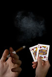 Cards and cigar in the male hands. With smoke on the black background Stock Photo