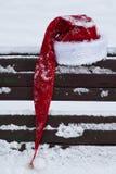 Cards den bakgrundsSanta Claus hatten på snö täckt bänk Royaltyfria Bilder