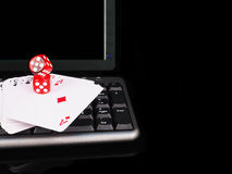 Cards, dice beside the keyboard. online card games concept Stock Image