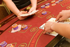 Cards game 2. Cards in hands are on red table in casino Royalty Free Stock Photography