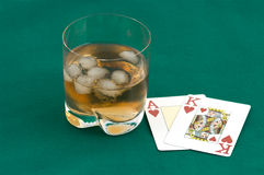 Cards and a glass of whisky. As the king of hearts and a glass of whisky with ice on green cloth Stock Photography