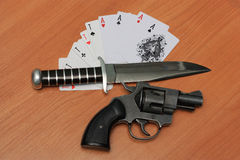 Cards, gun and knife. On a wooden desk Royalty Free Stock Photo