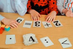 Cards with numbers lie on the table in front of children. mathem royalty free stock image