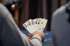 Cards in player's hand. Casino, gambling, poker, people and entertainment concept - close up of poker player with playing cards and chips at green casino table Stock Images