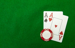 Cards showing pair of aces with chip on green Royalty Free Stock Image