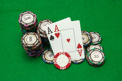 Cards showing pair of aces with chips on green Stock Images