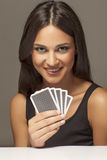 Cards and smile. Beautiful attractive girl holding poker cards and posing with a smile Royalty Free Stock Images
