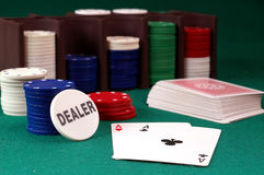 Cards and  stack of Poker chips. Nd   and dealer button on a green background Royalty Free Stock Image