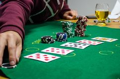 Poker chips with playing cards on a green table. Cards are in the table and betting were made. Some chips grouped and the are five cards to show Stock Images