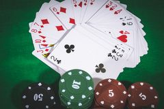 Cards on the table. Person playing poker and looking at cards , risk game poker table during a game. Chips, money and cards on the table Stock Photo