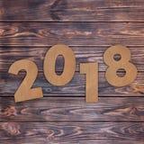 Cardstock nummer 2018 lyckliga nya år undertecknar över tabellen 3d framför Arkivfoton