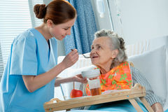 Care. Senior woman 90 years old being fed by a nurse royalty free stock images