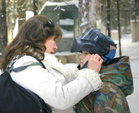Care. The mom helps the son put on the protective helmet to play paintball Royalty Free Stock Image