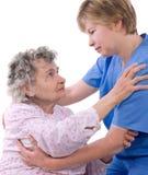 Care. Nurse helps the senior woman get up Stock Image