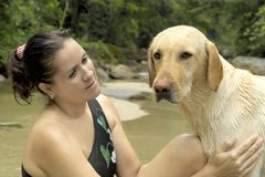 Care. Female and dog having a good time at the river stock photography